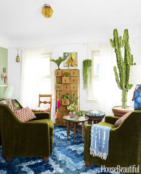 The living room is anchored by a tall euphorbia plant, which is similar to a cactus but needs less sunlight. The Fable rug is from Blakeney's collection for Loloi, the curtains are from Ikea and the rods are from Lowe's.