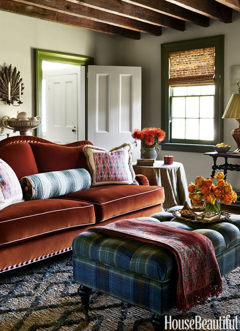 The custom sofa is covered in a Schumacher velvet and the Ballard Designs ottoman in a Rogers & Goffigon tartan. The trim painted in Benjamin Moore's Great Barrington Green.