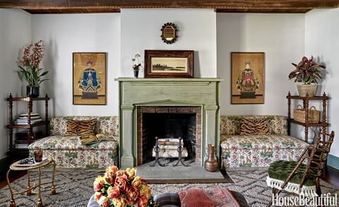 "<p>The living room's banquettes, in Pierre Frey's Ismaelia, flank a mantel with a combed faux finish by Dean Barger. ""We don't do animal prints often,"" Maxwell Foster says of the pillows. ""But Scalamandré's Tigre velvet is so luxe and warm, it worked here."" The 1876 chair is by George Jacob Hunzinger. A Bunny Williams for Dash & Albert rug was cut and trimmed to fit around the hearth.<span class=""redactor-invisible-space"" data-verified=""redactor"" data-redactor-tag=""span"" data-redactor-class=""redactor-invisible-space""></span></p>"