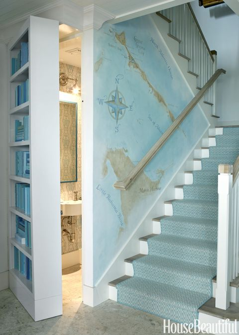 "The powder room's swinging door houses a color-coordinated bookcase. Artist Judy Mulligan painted a map of Guana Cay that Watson says includes ""the house, the family's favorite bar and places they like to take their boat."""