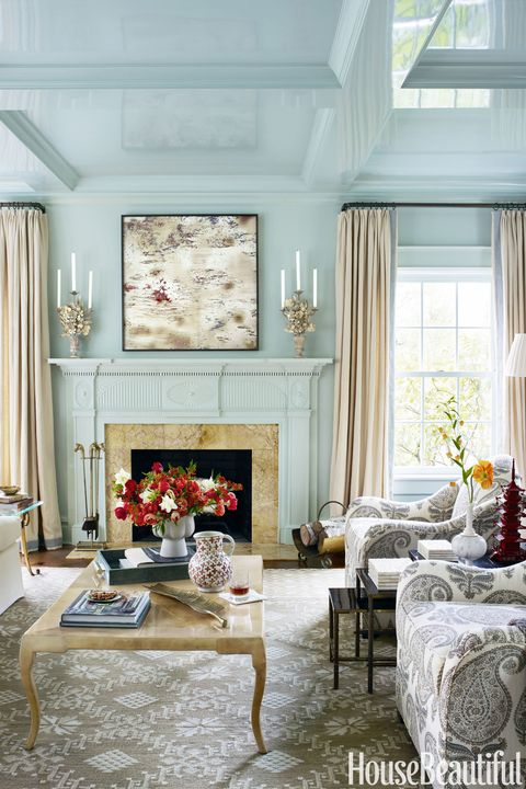 In the living room, custom-colored lacquer was applied for a sleek, unified surface. The Pierre armchairs from Bunny Williams Home are in a Jasper fabric by Michael S. Smith. The photograph over the mantel is by William T. Hillman.