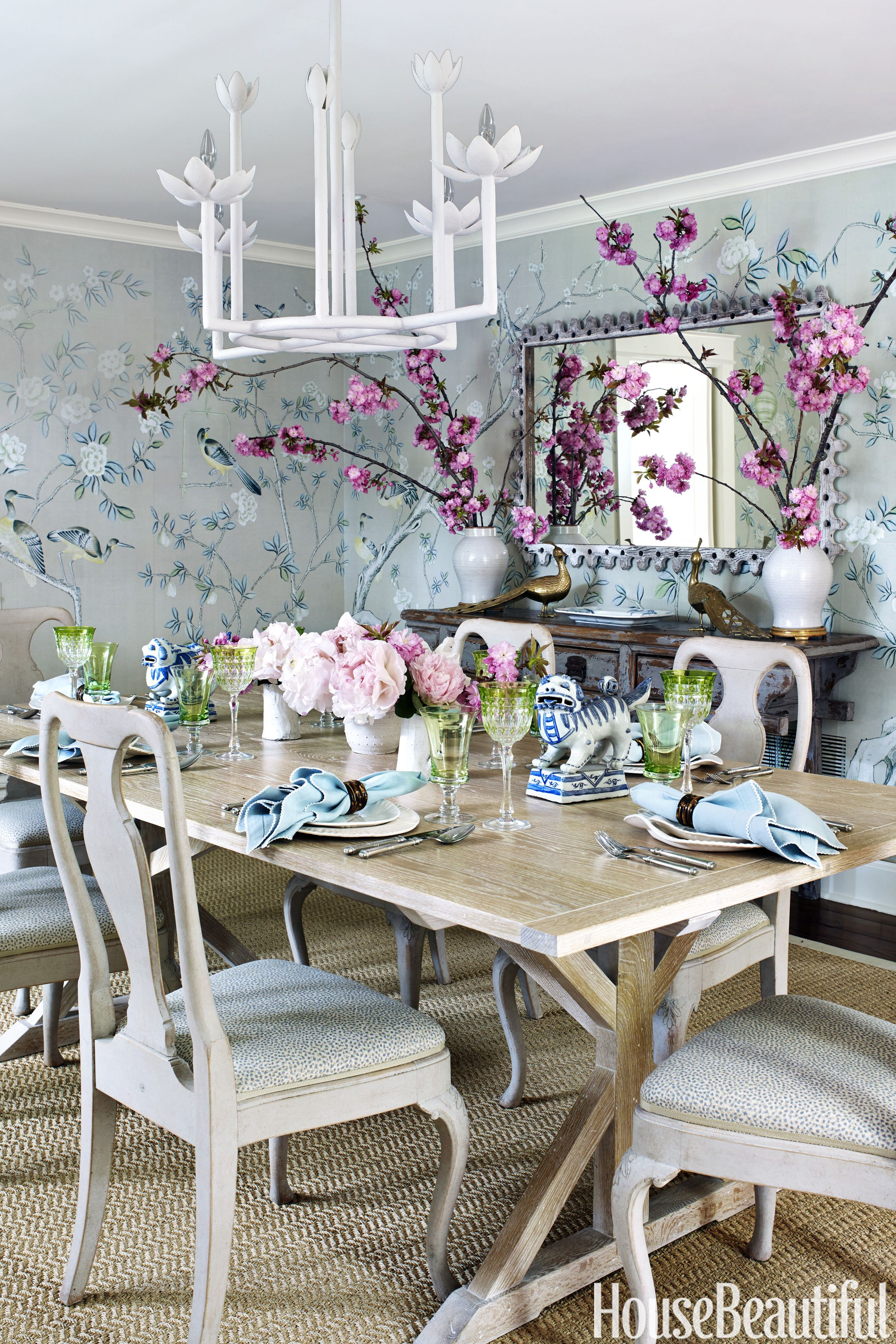 "De Gournay's hand-painted chinoiserie tea paper on the walls gives the dining room its dazzle, while Dan Mosheim's custom cerused-oak farm table acts as a gracious supporting player. The client bought the mirror at an antiques show. ""It's perfect,"" Watt says. ""It has a great shape, but it's not a big gilt thing taking attention away from the paper."" The antique Swedish chairs are covered in a Peter Fasano linen."