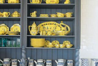 quimper dinnerware in blue cabinet designed by joanne hudson
