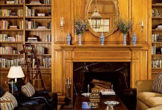 traditional library with giltwood mirror above mantel