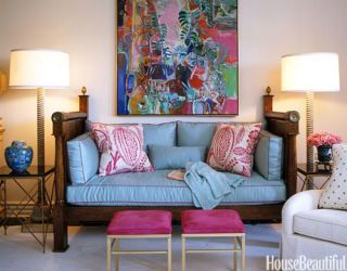 living room with blue daybed and pink footstools