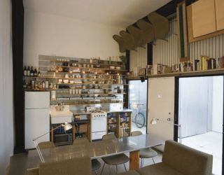 kitchen with steel table top and shelving above sink and oven as well as a book shelf above doors and chairs hanging on wall
