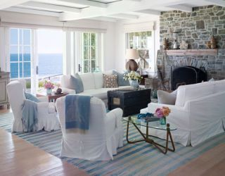 living room with large stone fireplace and white slip covers on furniture and blue striped run