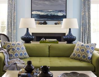 green and blue living room with green sofa and painting of the ocean