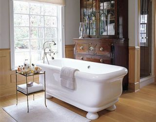 bathroom with large white tub and antique cabinet