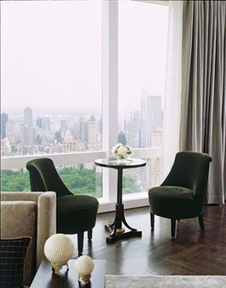 Green velvet chairs on a parquet  floor.