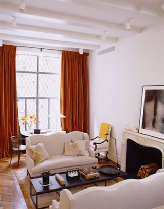 Orange curtains in Ina Garten's white living room.