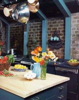 pots hang from overhead store, island with pull out drawers and flower on counter