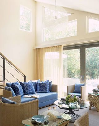 living room with blue couch and big windows