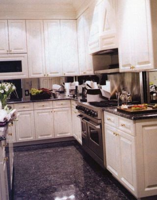 white cupboards, stainless steel appliances, black tiled floor