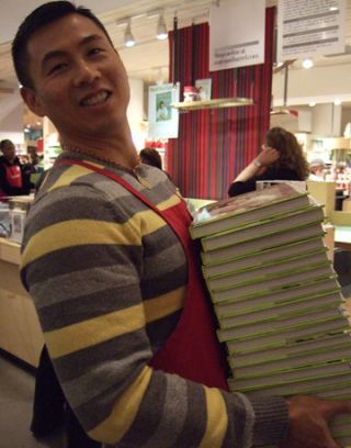 store worker carrying stack of books