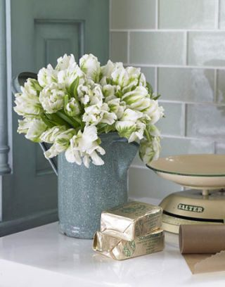 tin with flowers and old fashioned weight on counter