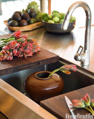 sink with vase and flowers and sliding cutting boards