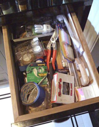 junk drawer with candles scotch tape and tools