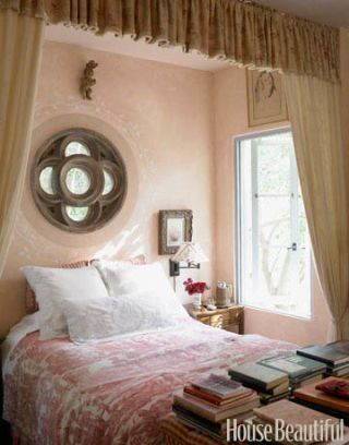 antique fabrics cover pink walled bedroom