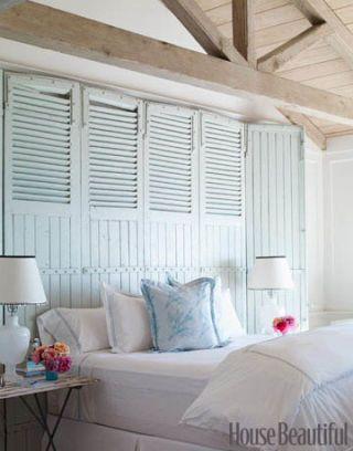 seafoam colored barn door headboard in white master bedroom