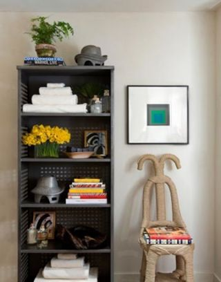 a shelving unit and chair in this master bath