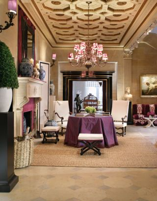 vestibule with table and chairs and fireplace and grand chandelier