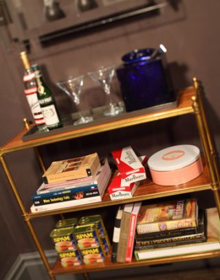 bar cart with bar essentials and retro necessities like cigarettes and spam and books