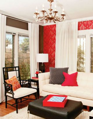 living room with white furniture and red patterned walls as well as black side tables and coffee table