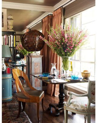 dining table with two chairs and large floral arrangement