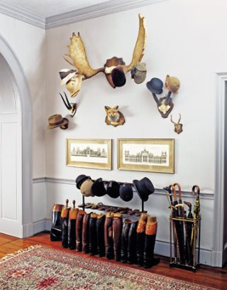 entryway with boots and antlers with hats hanging from them
