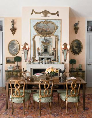 dining room area with patina colored slipcovered chairs, and mirror above the mantel
