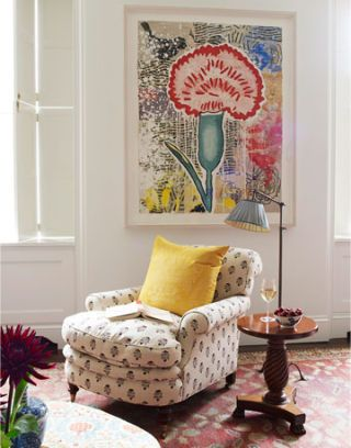 pink flower painting above comfy reading chair and lamp