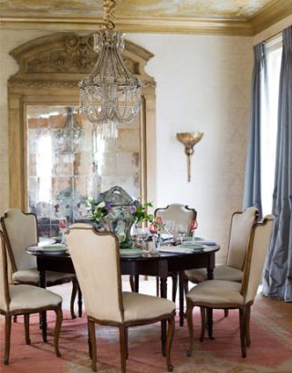 formal dining room with crystal chandelier and large mirror and pink carpet