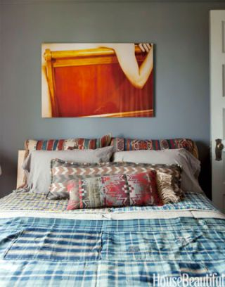 bright photograph print hanging above bed on gray walls