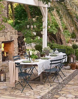 patio with outdoor fireplace and dining table