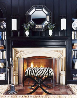 black painted library with fireplace and zebra print stool