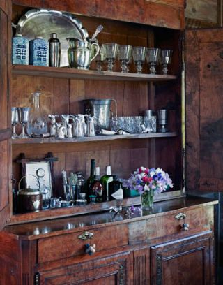 antique cabinet with cocktail glasses set up as a bar