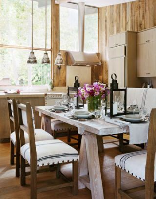 dining room with wood panels and a big window next to the kitchen