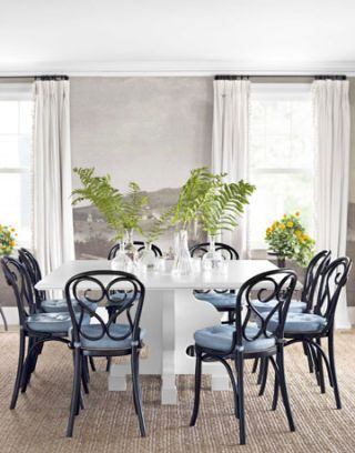 white table surrounded by black chars with blue cushions