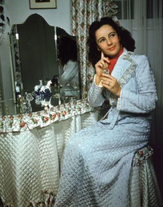 woman sitting down next to a mirror