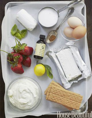 ingredients for baking a cheese cake with goat cheese eggs basil strawberries lemon and graham crackers