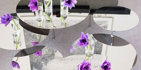circular mirrored tables with purple flowers in water on top
