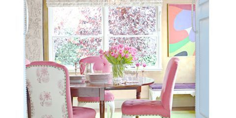 a dining room with a gold ceiling a green rug and pink chairs