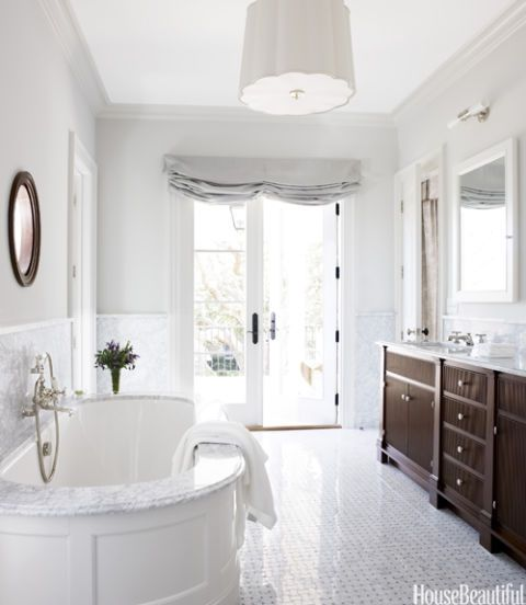 white bathroom with oval tub and polished tile