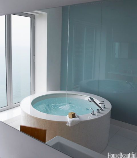 circular bathtub in white bathroom with spout coming from the ceiling