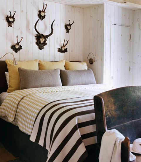a guest bedroom with antlers on wall a striped blanket and a bench at the foot of the bed