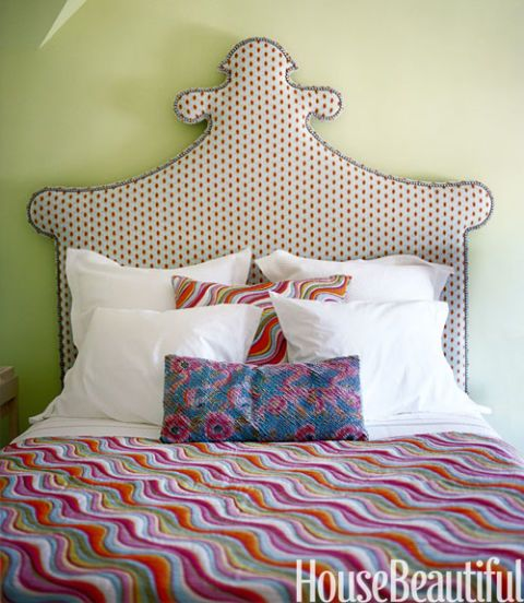 victorian bed in front of green wall
