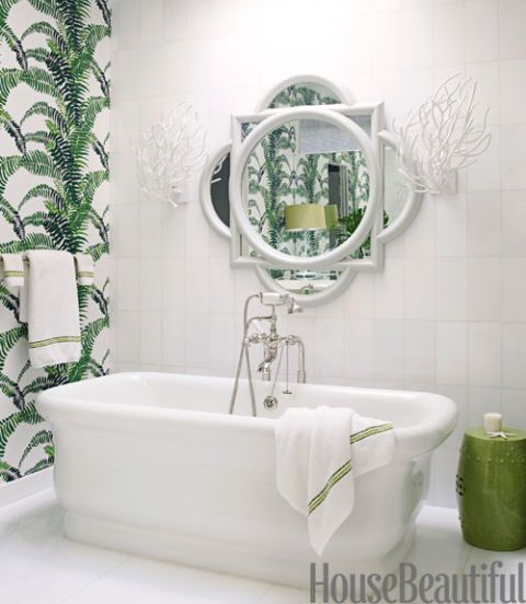 white bath tub in room with green and white wallpaper