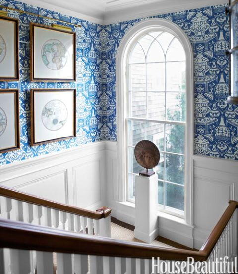 Vibrant blue wallpaper and elegant wainscot paneling on a stair landing in a traditional home. #staircase #wallpaper #brightblue #decor #traditional
