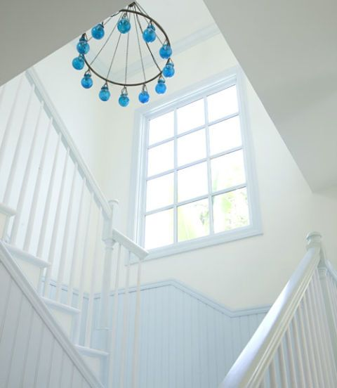 white and light blue stairway with window and blue glass chandelier